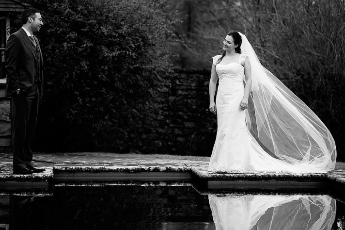Black and white wedding photo- bride and groom smile at each other outside by water