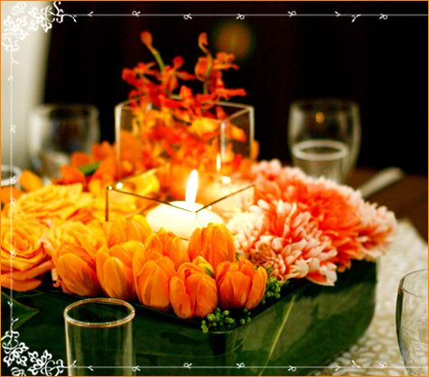 Orange yellow and green wedding flower artistry beautiful low centerpiece orange flowers surround glass votice holder and candle mightylinksfo