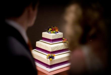 White wedding cake purple ribbon small floral details in yellow red