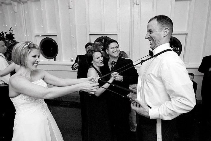 Black and white photo of bride having fun with groom's suspenders at wedding reception