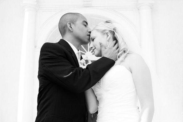 Groom in black suit kisses bride in strapless dress.