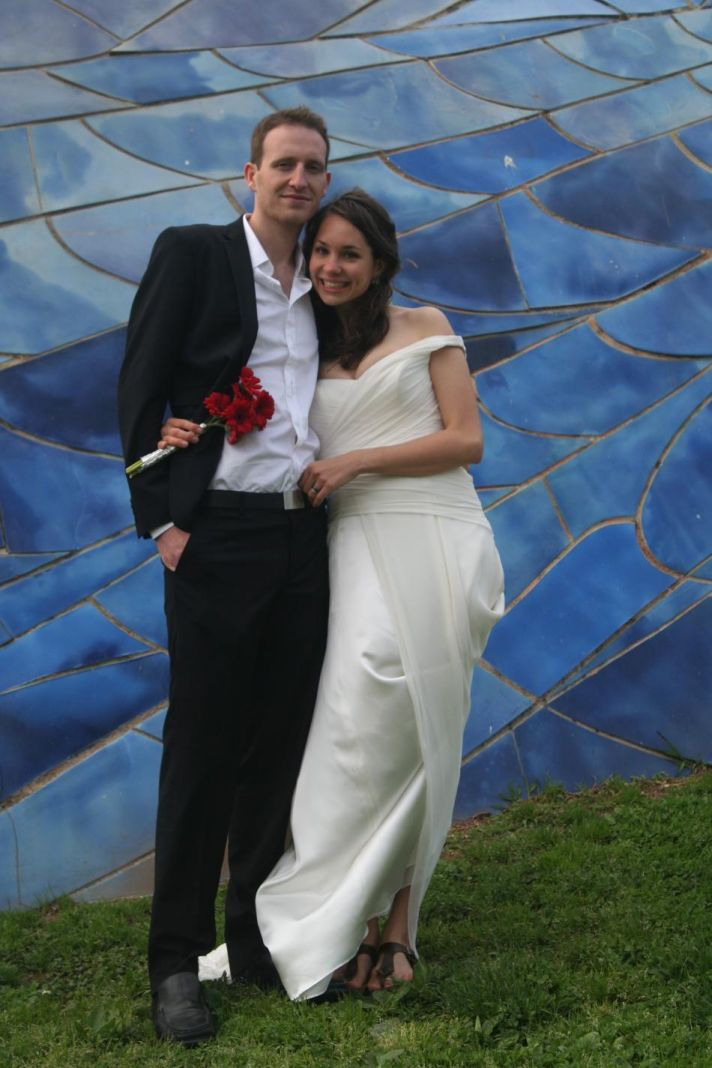 A bride with long brown hair worn down stands next to her casual groom while wearing a simple white