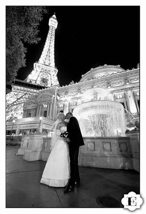 Black and white wedding photo- Bride and groom kiss with Eiffel Tower in background