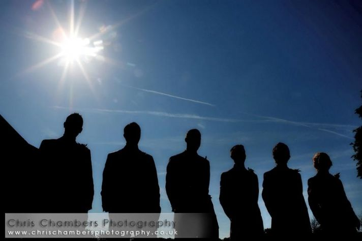 Groom, best man, and groomsmen stand together outside, perfect blue sky and shining sun in backgroun