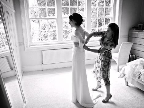 Gorgeous black and white wedding photo, bridesmaid zips back of wedding dress for bride