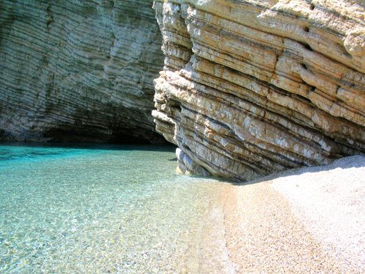 The crystal blue water is striking next to the brown sandstone rocks on this Greek beach.
