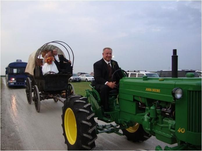 Bride and groom ride to wedding reception on John Deere tractors