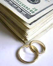 This pile of money with two gold wedding rings next to it shows us that money and weddings are relat