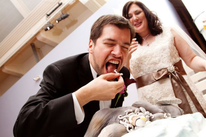 The bride in a white dress with brown sash seems to be looking on in horror as her groom eats the St