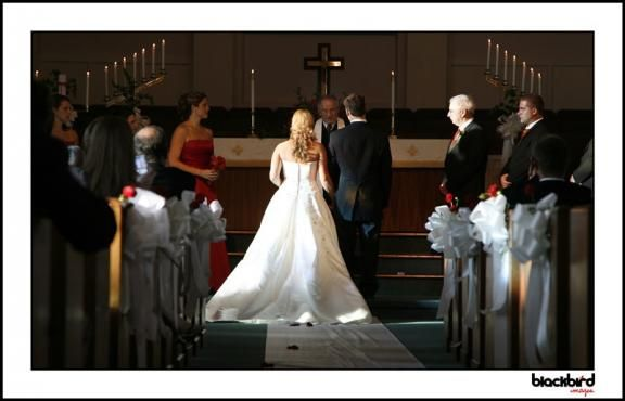 The red bridesmaid's dress and traditional full-skirted wedding dress are perfect for this elegant c