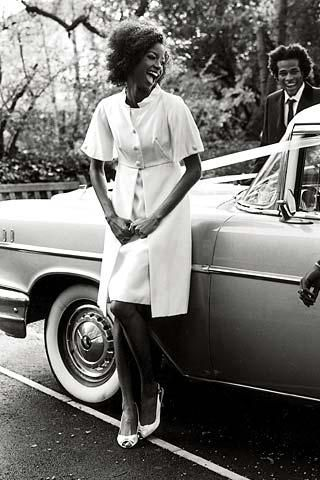 Beautiful bride-to-be leans against antique car, wearing white short sleeve coat dress