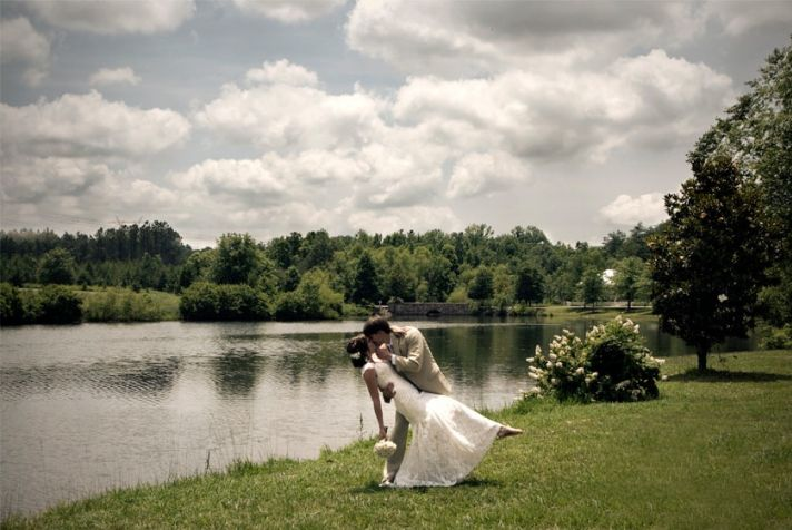 The bride in her casual, lace, white wedding dress and groom in his tan suit kiss in the green field