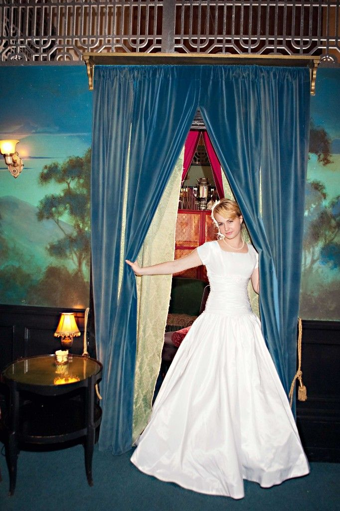 The bride's 1950s style wedding dress is perfect with the blue curtain.