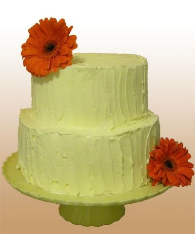 This green two tiered cake is simply decorated with orange daisies.