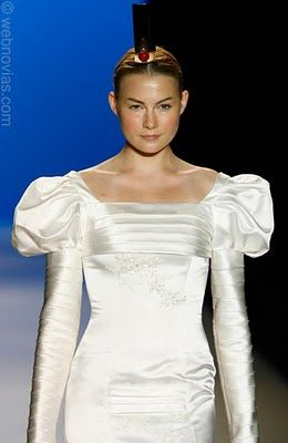 This white satin wedding dress features a square neckline and long sleeves.
