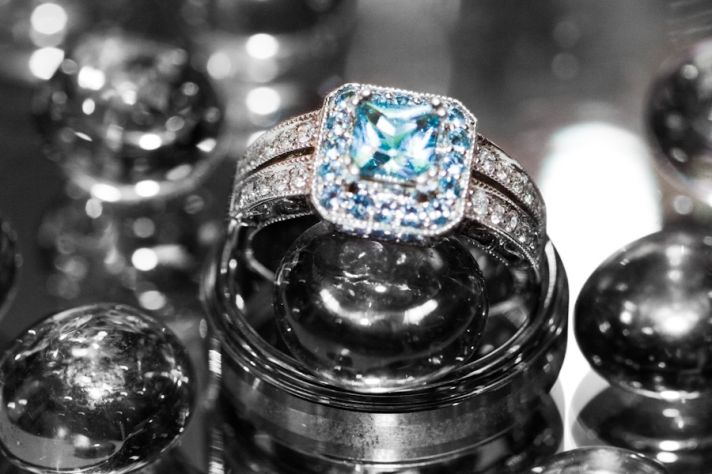 Stunning cushion cut diamond engagement ring sits atop men's wedding band