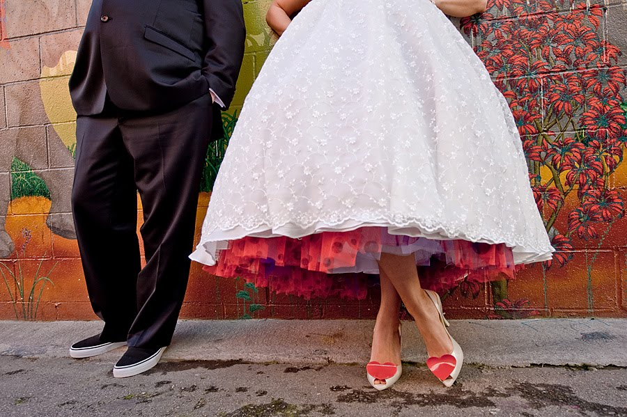 Bride wears tealength white wedding dress with red purple polka dot tulle