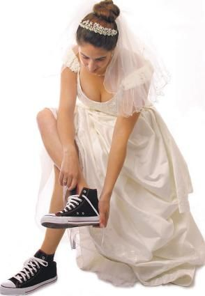 This bride is ready to exercise in her traditional white wedding dress with a long veil, updo and ti