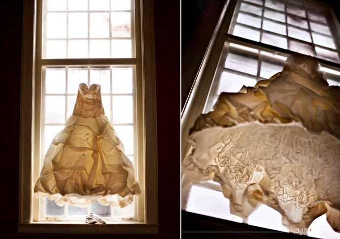 Bride's dramatic ivory ballgown wedding dress hangs artistically in window