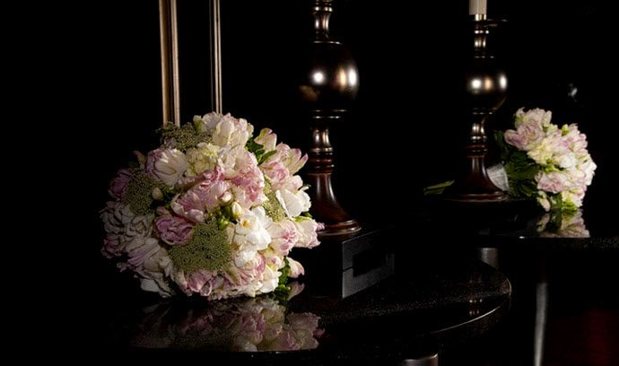 Brides pastel bridal bouquet (light pink, ivory, green, yellow) lays on dark wood table