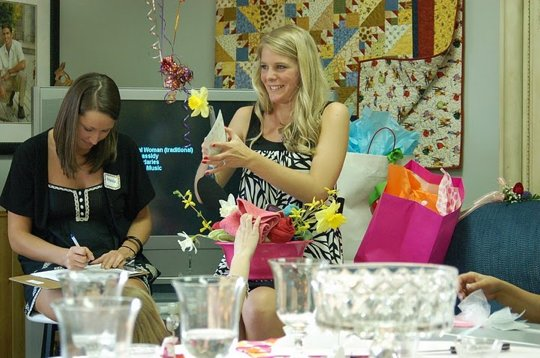 This blonde is opening a variety of bridal shower gifts in front of her friends and family.