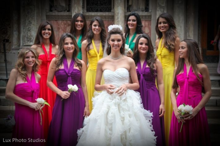 This bride has many bridesmaids all wearing different, brightly colored dresses behind her.