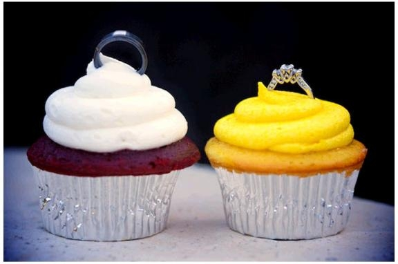 artistic-wedding-ring-shot-grooms-wedding-band-brides-engagement-ring-sit-atop-yellow-white-frosting-on-wedding-cupcakes
