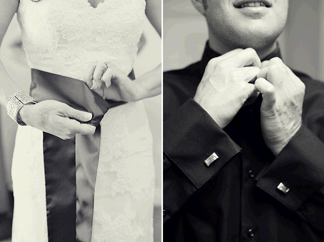 Bride ties the black sash on her ivory lace wedding dress groom buttons up