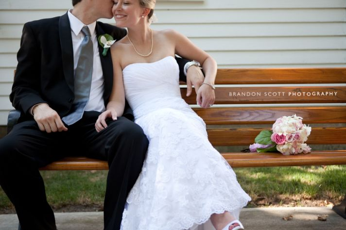 Bride in white lace wedding dress sits with dapper groom (in black suit) on park bench