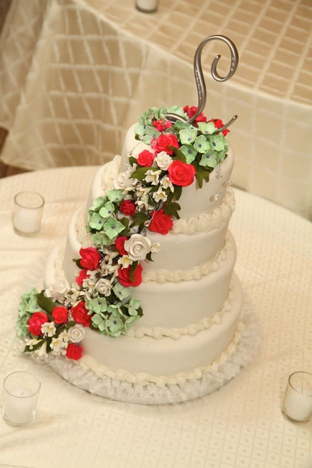 This beautiful four tired white wedding cake is decorated with small red, green and white flowers