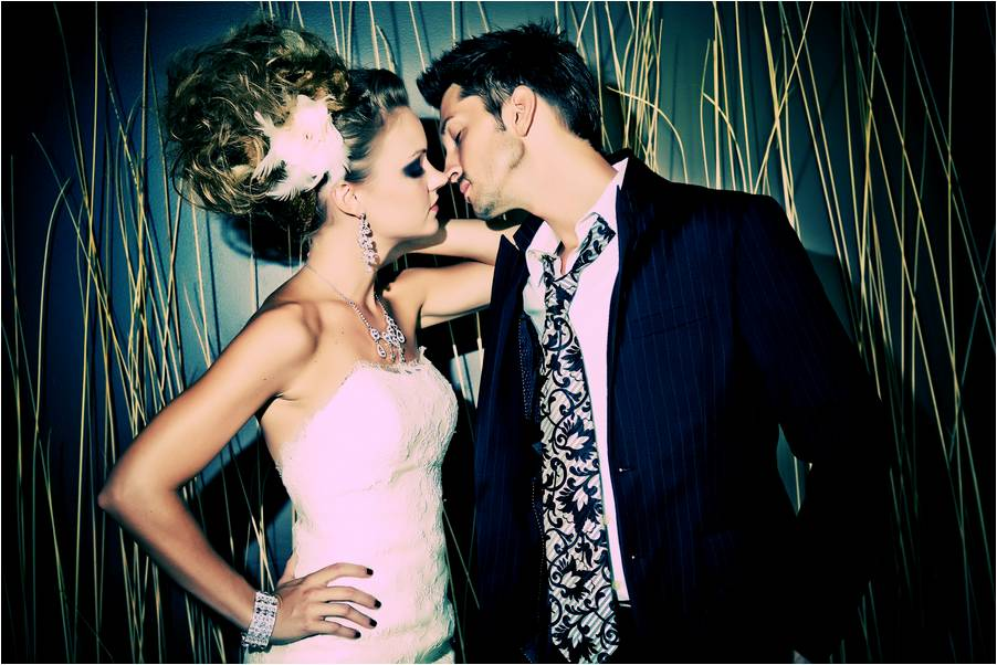 Edgy bride in strapless wedding dress kisses casual rock n roll groom