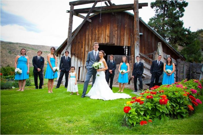 Bride and groom pose outside of rustic wedding venue with wedding party