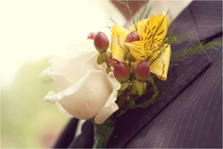 Groom wears pin stripe suit and ivory, yellow, berry red boutonnière