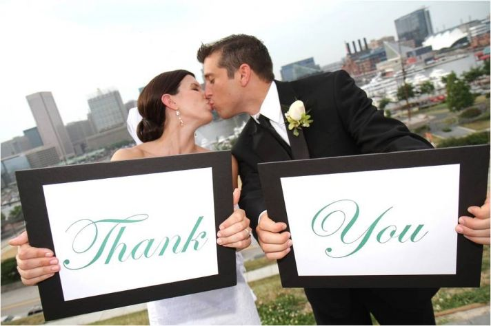 Bride and groom kiss, hold Thank You signs, with Baltimore skyline in background