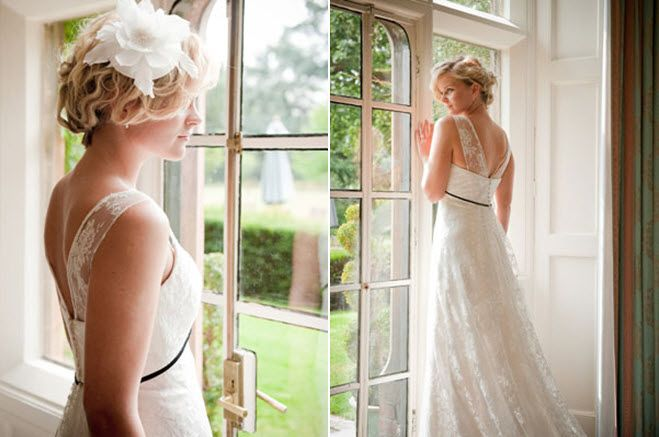 Vintage-chic bride in lace a-line wedding dress peers out window