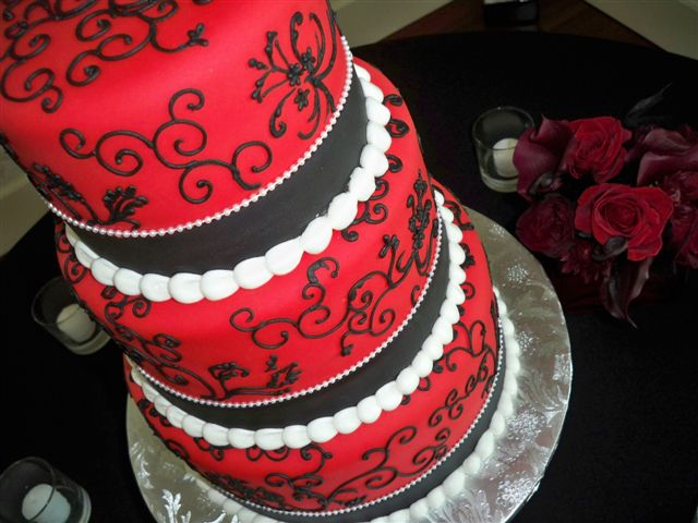 This three tier red and black wedding cake has white piping