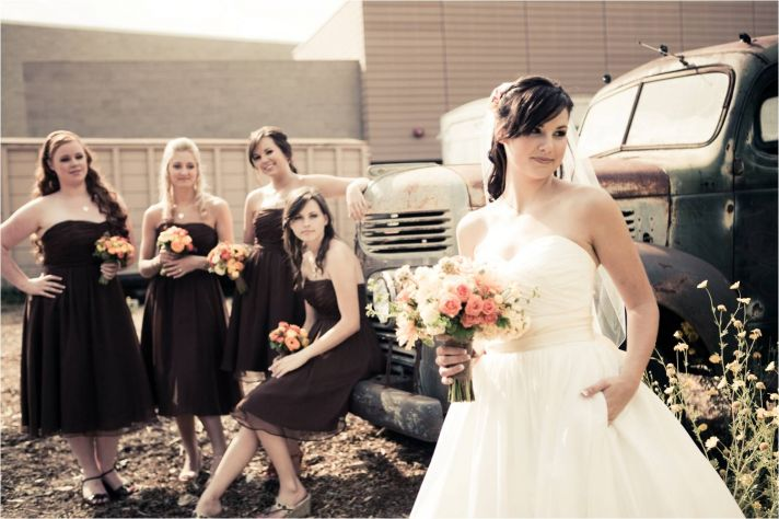 Bride in classic ball gown wedding dress poses with bridesmaids, wearing chocolate brown strapless d