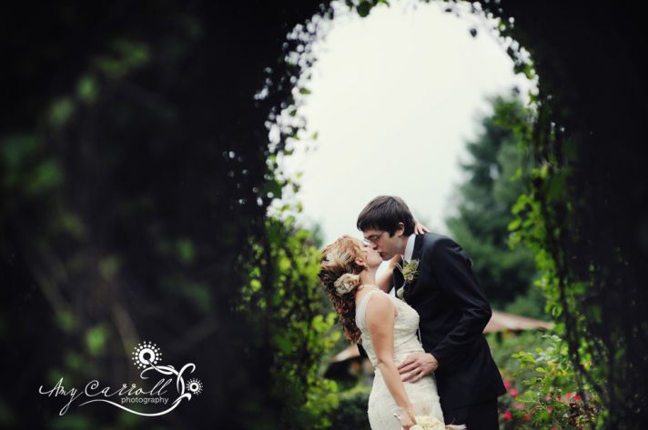 Vintage bride and groom kiss beneath leafy arch in romantic garden