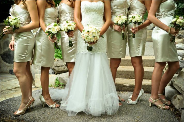 Bride wears romantic lace wedding dress, bridesmaids wear strapless champagne cocktail frocks