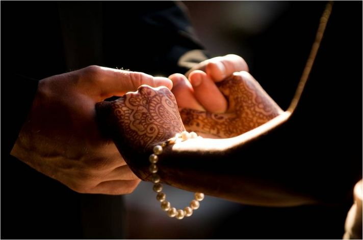 Bride's henna-adorned hands are placed in groom's hands while taking their vows