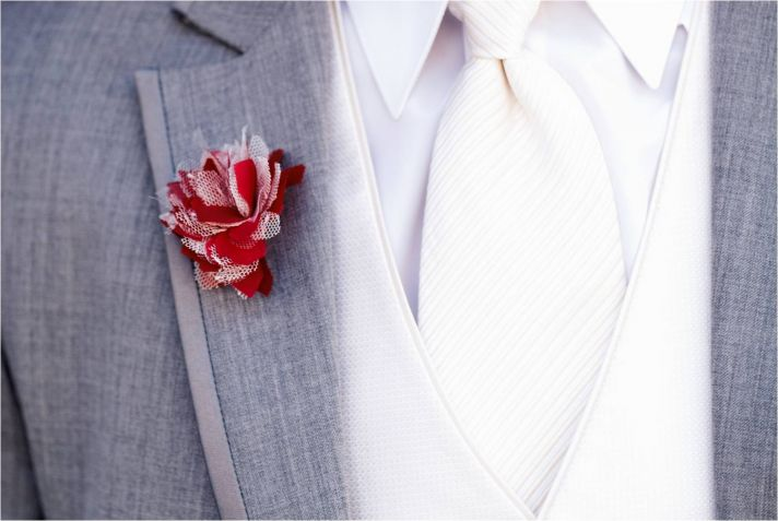 Groom wearing grey suit white shirt and tie and red and white boutonniere