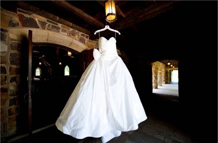 white-ballgown-strapless-wedding-dress-hangs-in-venue-castle