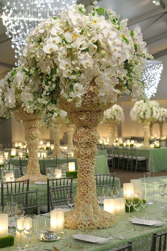 Dramatic high floral topiary with ivory orchids to achieve a elegant, sophisticated wedding vibe