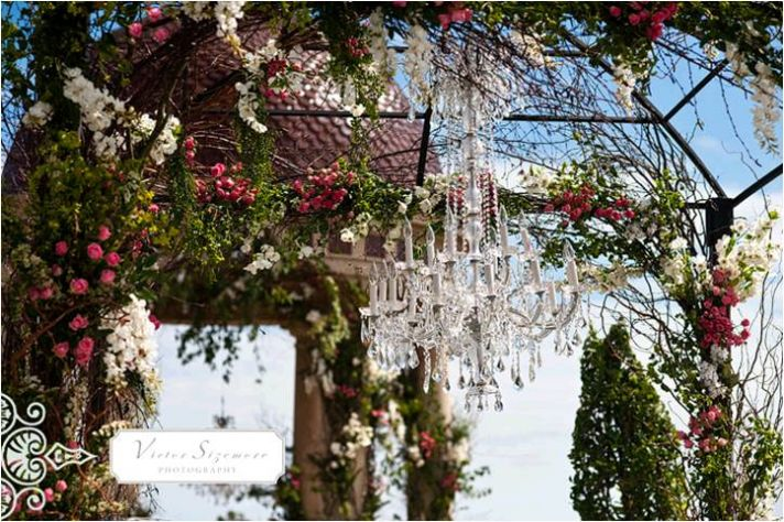 Outdoor California wedding venue with floral-adorned arch and chandelier