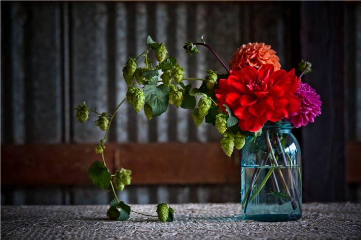 Fluffy red, orange and pink wedding flowers arranged in vintage mason jar