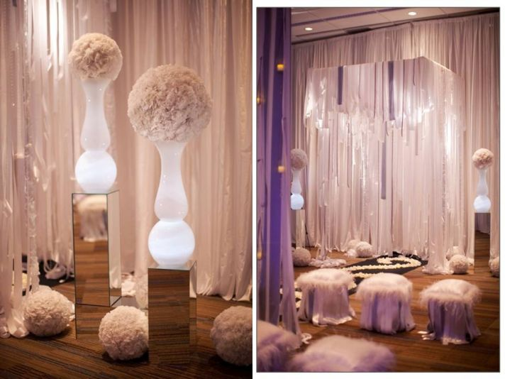 Frosted glass vases illuminated with white wedding flower arrangement on top; romantic wedding cerem