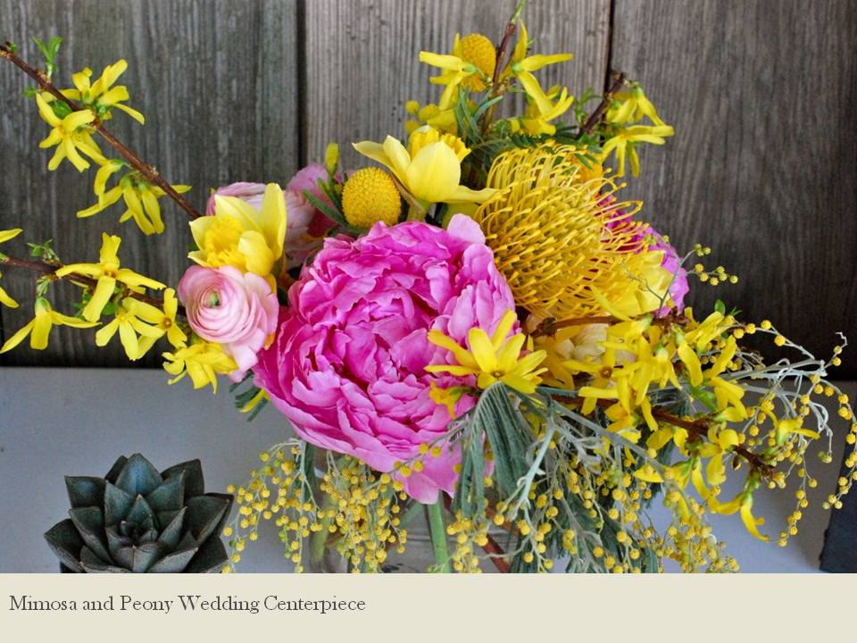 Hot pink peonies and yellow mimosa in wedding flower arrangement