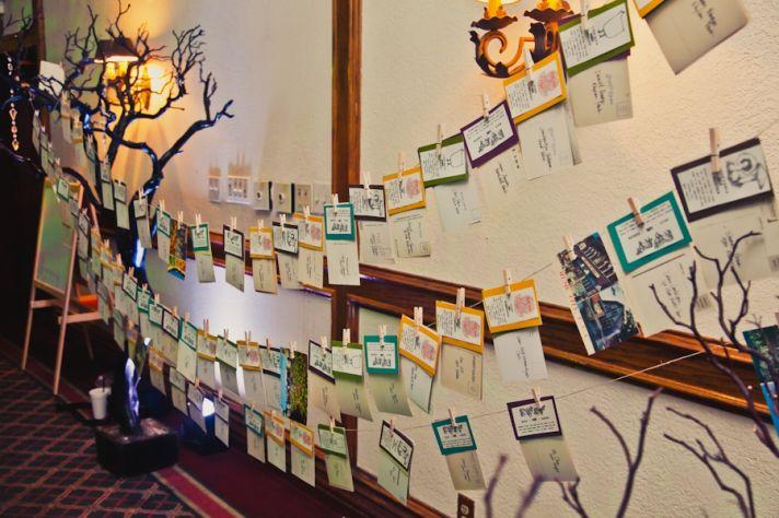 Unique wedding reception escort table- escort cards hang from clothesline