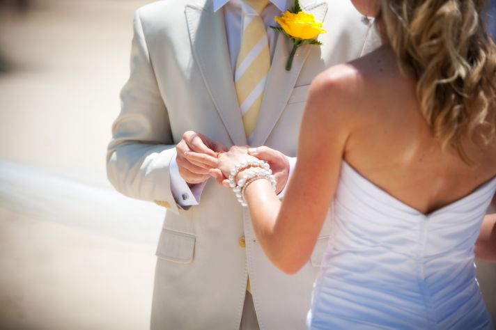 Destination wedding ceremony on the beach- bride and groom exchange wedding rings