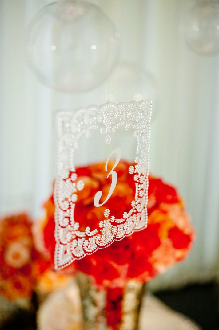 Orange wedding reception centerpieces with lace-adorned table numbers
